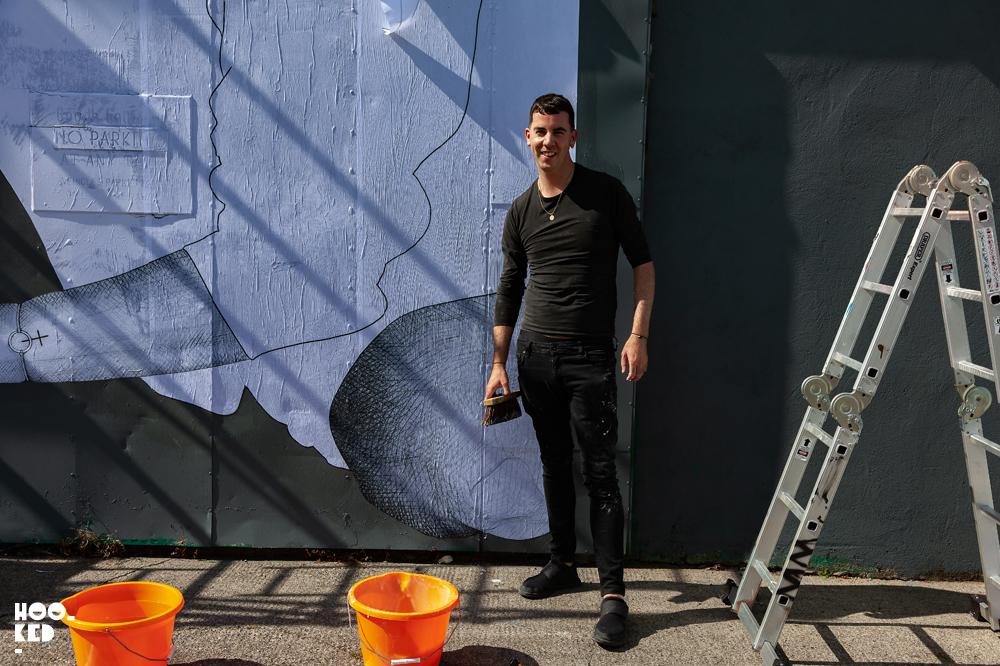 Portrait of by Irish artist Joe Caslin working on his mural for Waterford street art festival