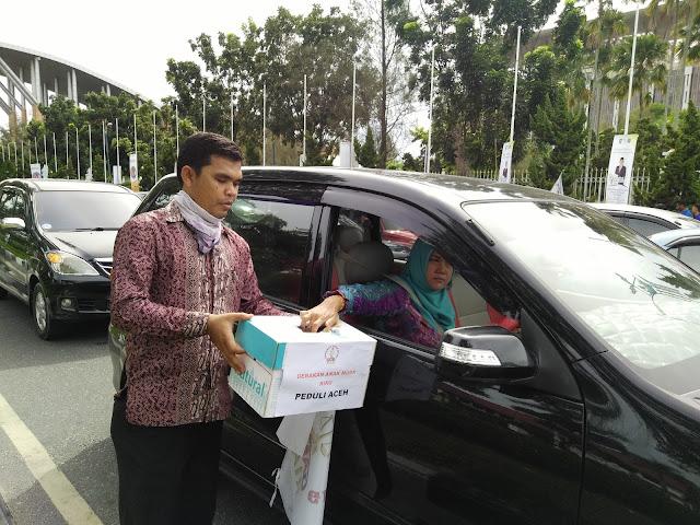 Sekjen GAMa Riau, Darussalim mengumpulkan dana dari pengendara mobil disekitar bundaran Tugu Zapin, Kota Pekanbaru, Jumat, 9 Desember 2016.