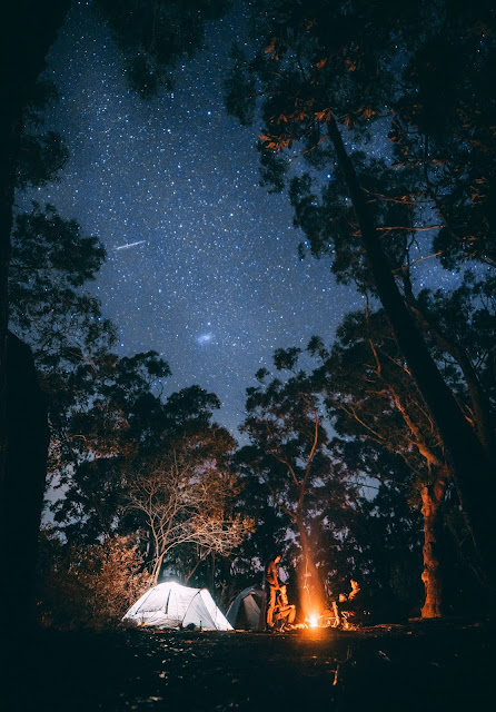 Illuminated tent under starry sky with campfire:Photo by Jonathan Forage on Unsplash