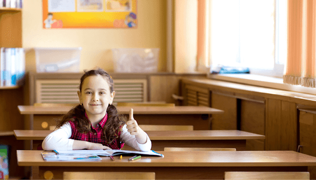 Photo of girl in classroom giving the camera thumbs-up.