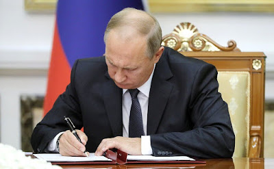 Vladimir Putin signing documents following Russian - Turkmenistani talks in Ashgabat.