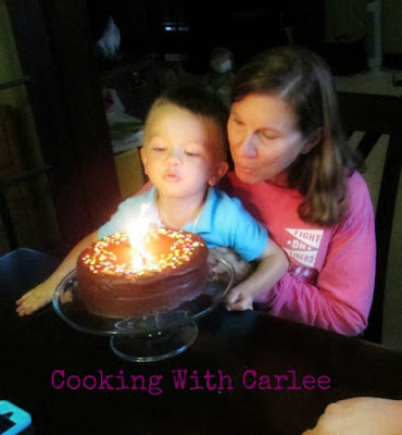 mimi and little dude blowing out the birthday candles on her birthday cake