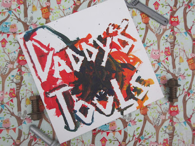 A small canvas, which has been painted by a child and reads 'daddys tools'