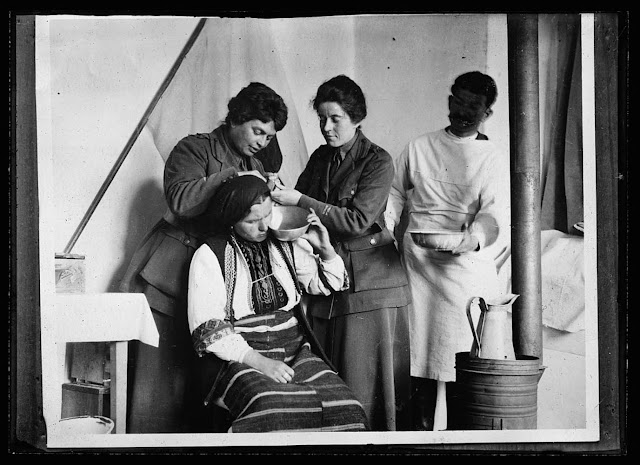 Serbians* never had the hospital habit, for the simple reason that there were no institutions to practice the habit on. This native woman of Monastir was induced to visit the American Red Cross hospital after suffering several days with an ear-ache. Dr. Eugenie Flod Keyes and Dr. Mabel Flood of the Red Cross staff are administering relief in the above picture. The Serbian woman is doubtful but patient. She is dressed in the native costume of Monastir, each town of the country having its own brocaded in bright colors. At this dispensary, 150 people are treated every day