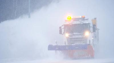 Plogbil med Sveviaskylt plogar väg i snöyra