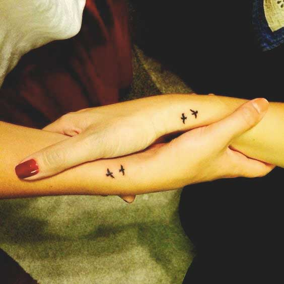 Small birds tattoos on wrist for sisters