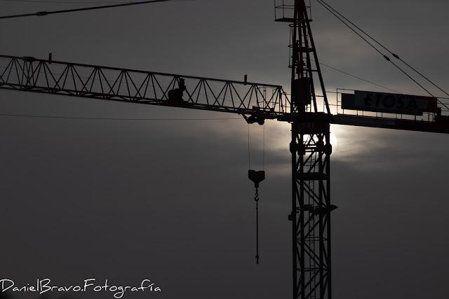 Imagen de una grúa de obra a contraluz, con el Sol detrás de ella.