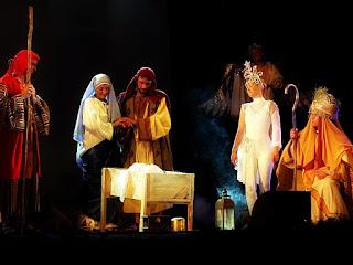 José e Maria, entre os Reis Magos e a Estrela Guia, olham para o menino Jesus na manjedoura.
