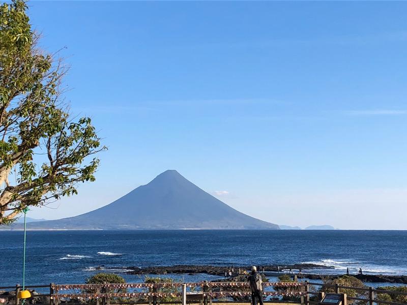 青い空と濃紺の海。遠くに山がそびえ立っています。