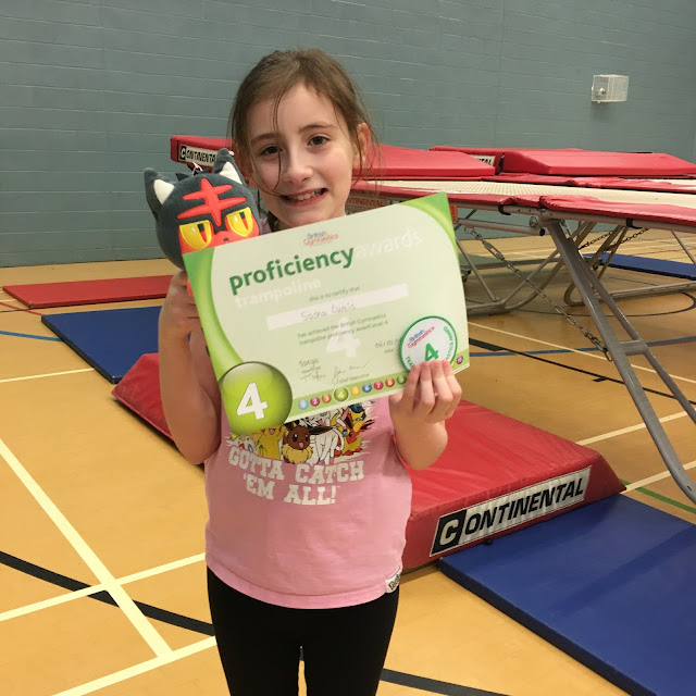 Sasha showing her badge and certificate