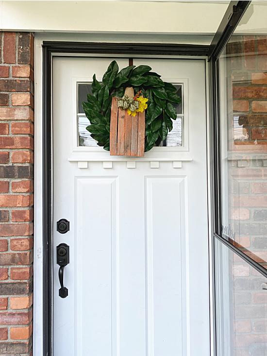 front door with wreath and pumpkin