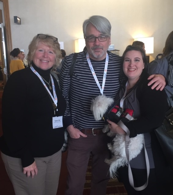 2 smiling women lean into smiling man in middle 1 woman is holding a service dog