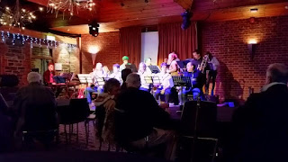 A jazz big band in between sets at a cosy indoor venue on a winter's night. There are approximately 14 people in the band comprising keyboard, drums, bass, trumpets, trombones and saxophones with the occasional clarinet, flute or flugelhorn.