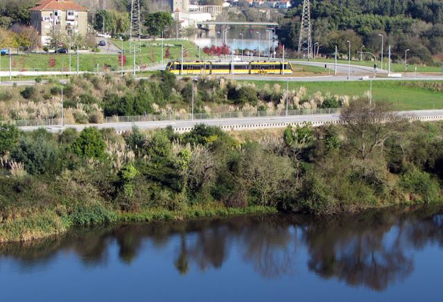 metro passando pela cidade de Vila do Conde e por vegetações à beira do rio