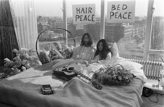 John Lennon and wife Yoko Ono in bed with peace cardboards