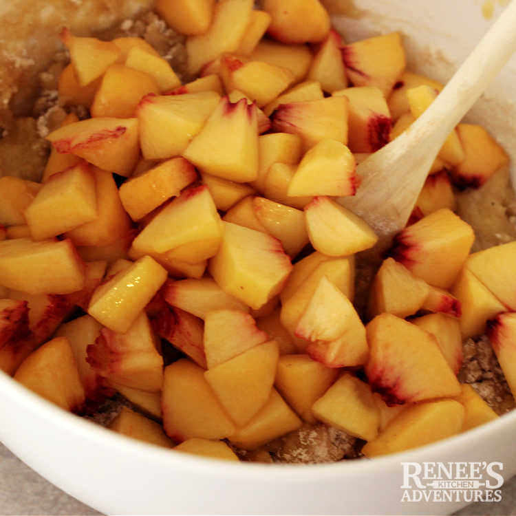 Peaches being folded into peach bread batter with wooden spoon