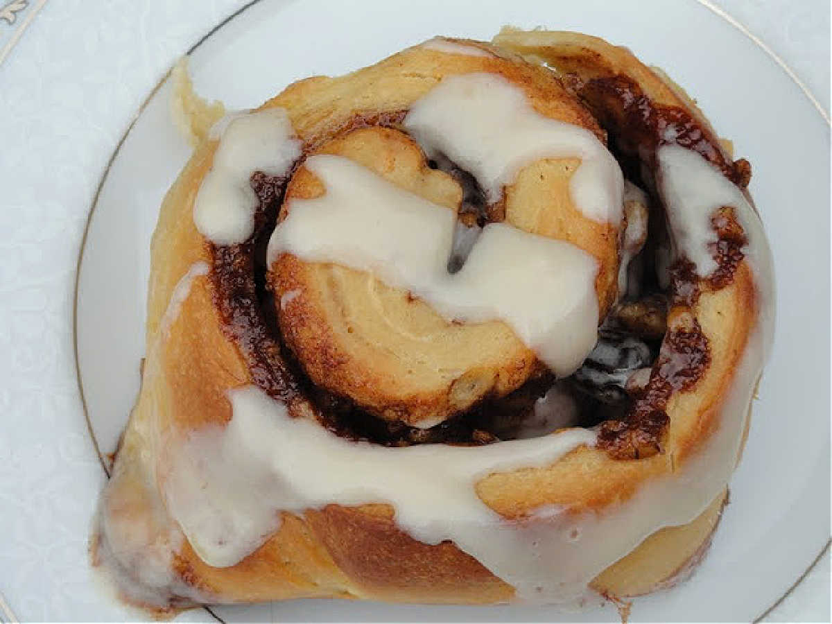 Worlds Greatest Cinnamon Rolls drizzled with Buttermilk Cream Cheese Icing on a white plate.