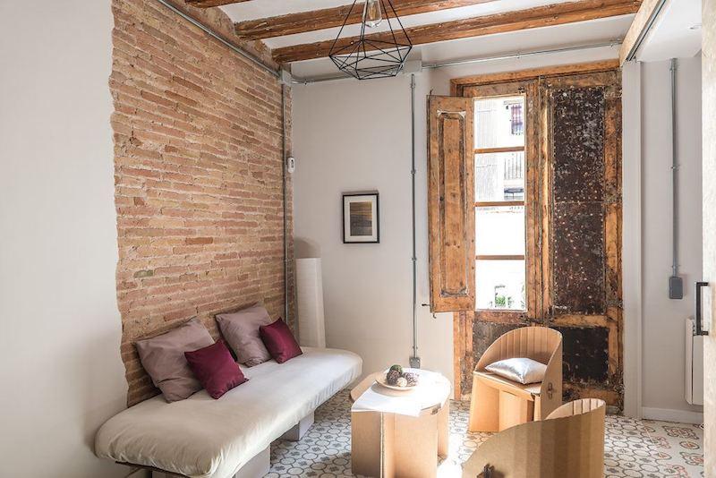 Apartamento con muebles de cartón y la instalación vista. Salón con sofá con base de cartón.