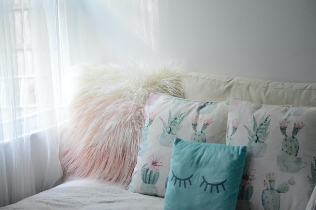 A bed with white bedding and an assortment of light coloured cushions next to a bright window with white voile drapes