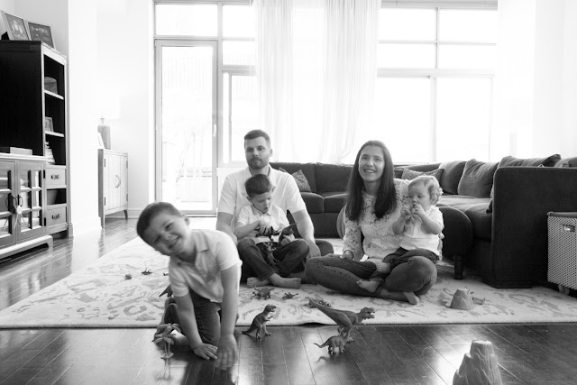 family in white and denim with dinosaurs sitting in living room at home family portraits