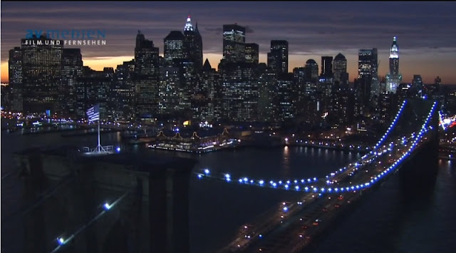 Photo of Lower Manhattan at sunset as seen from above the Brooklyn Bridge