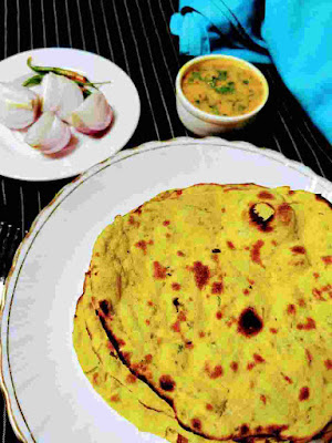 Serving Missi roti with onion, green chilli and dal in background