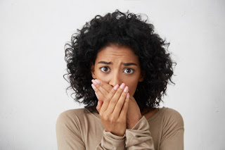 negra mulher cabelo cacheado estressada com mão na boca