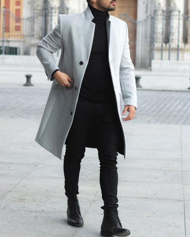 A man in long coat, high neck, Chelsea boots and slim fit jeans.