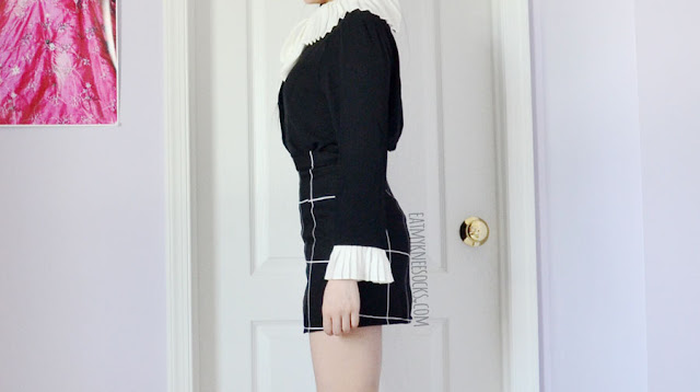 Details on the ruffled pleated black-and-white self-tie long sleeve button down blouse from Twist X Turn, paired with a black grid bodycon skirt.