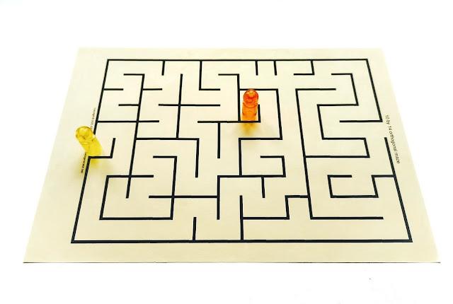 na zdjęciu widzimy labirynt wydrukowany na żółtej kartce A4 na brzegu labiryntu stoi pionek a wewnątrz labiryntu drugi