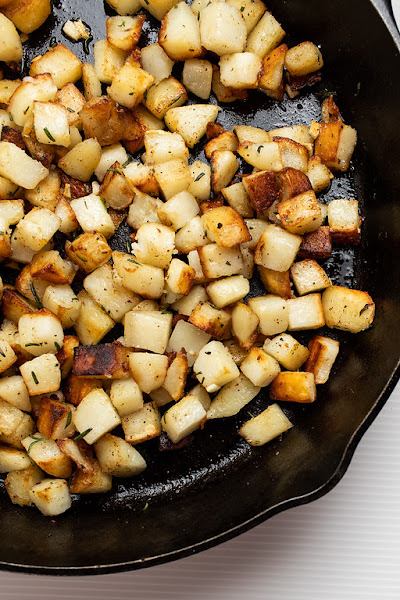 Top view of country fried potatoes in a cast iron skillet.