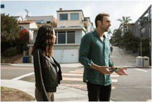 Man and woman walking on the sidewalk talking