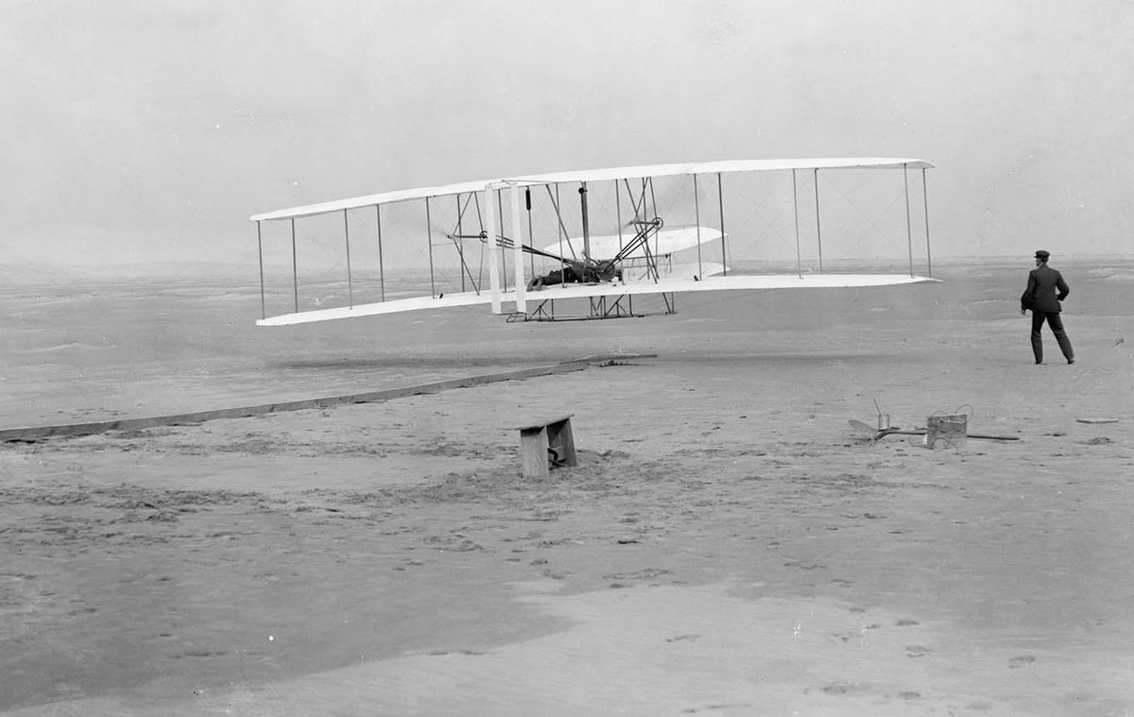 First flight: 120 feet in 12 seconds, on December 17, 1903. This photograph shows man's first powered, controlled, sustained flight. Orville Wright at the controls of the machine, lying prone on the lower wing with hips in the cradle which operated the wing-warping mechanism. Wilbur Wright running alongside to balance the machine, has just released his hold on the forward upright of the right wing. The starting rail, the wing-rest, a coil box, and other items needed for flight preparation are visible behind the machine. Orville Wright preset the camera and had John T. Daniels squeeze the rubber bulb, tripping the shutter.