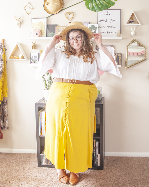 An outfit consisting of a straw boater hat, a white ruffle neck line off the shoulder top with 3/4 bell sleeves tucked into a button up yellow midi skirt and brown d'orsay flats.
