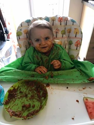 A baby covered up in a large long sleeve bib which covers the edge of the high chair too. Food is smeared everywhere