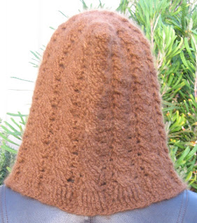 Jodie's cabled alpaca hood being worn. Rear view.  One can see how the cable pattern begins in the ribbed bottom edge and works its way up the hood.