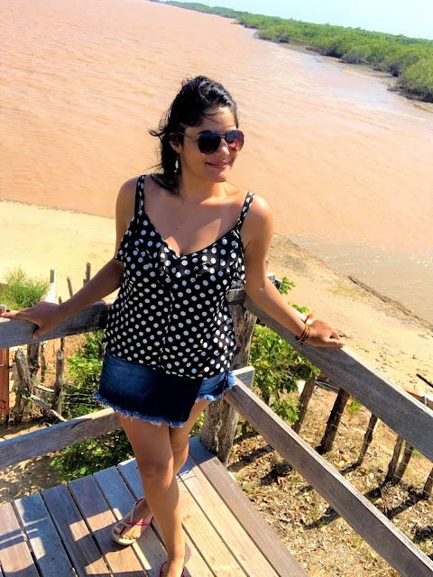 mulher morena de oculos escuros, short jeans e blusa preta de bolinhas, em um mirador do delta do rio parnaiba