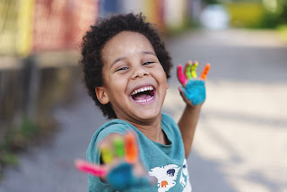 Young boy laughing, with paint on his hands