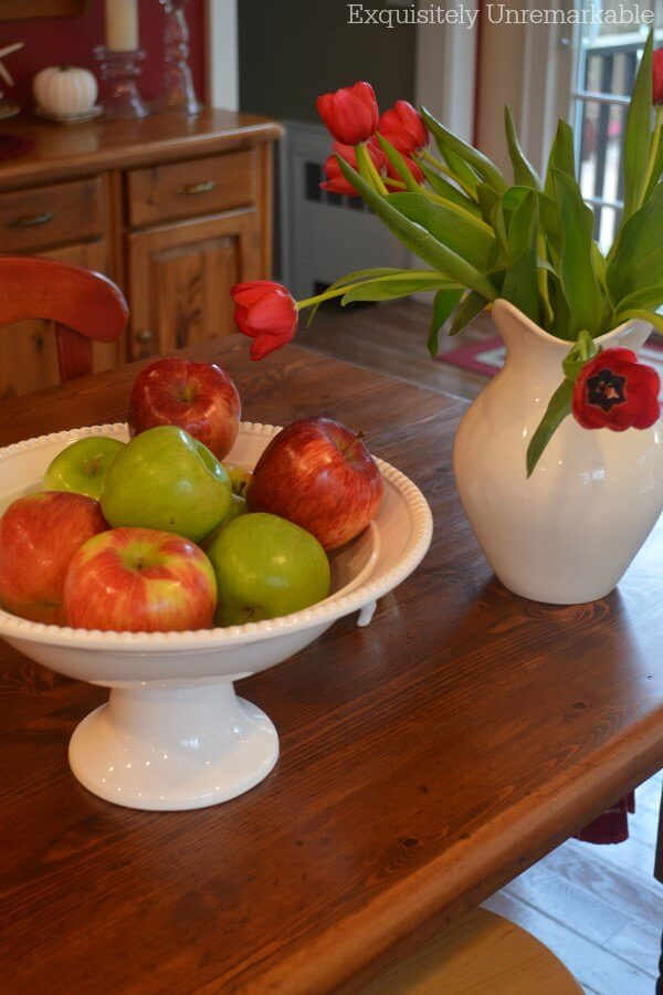 Farmhouse Table DIY with apples and flowers in white bowls and pitchers