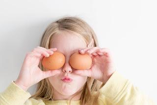 bambina bionda che tiene 2 uova davanti agli occhi
