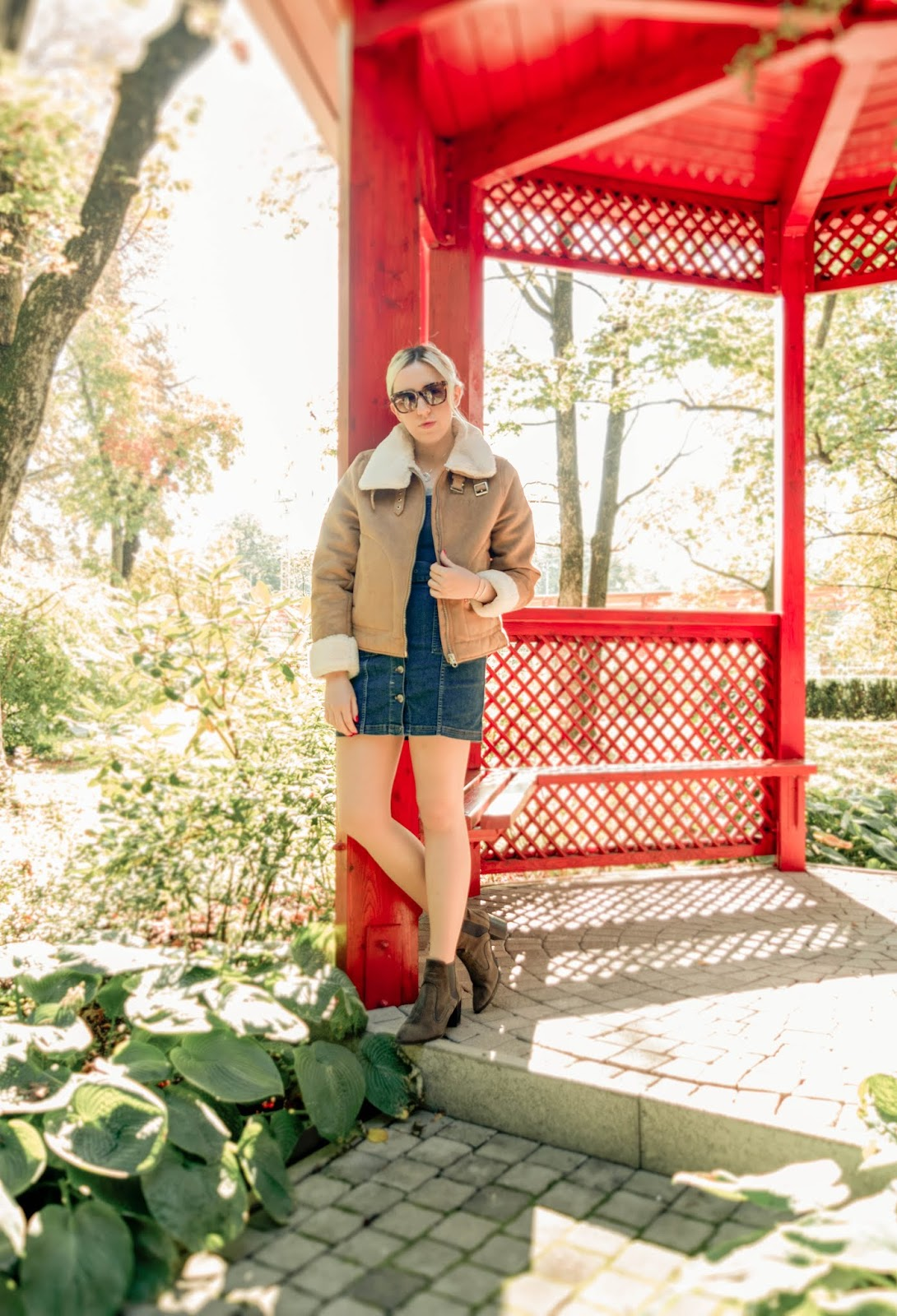 Girl wearing a denim pinafore dress, aviator jacket and ankle boots in Botanical garden