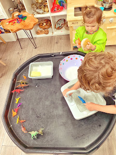 tuff tray with wash bowl and dinosaurs with children washing the toys