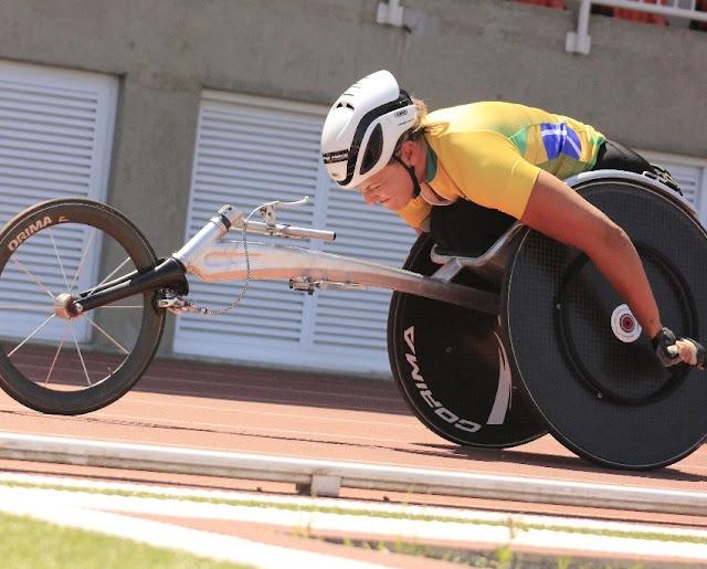 Jéssica Messali, de capacete branco, camisa branca com detalhes da bandeira do Brasil e cadeira de rodas, treinando no CT paralímpico