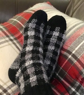 Foot with socks knitted in plaid pattern resting on plaid-patterned pillow
