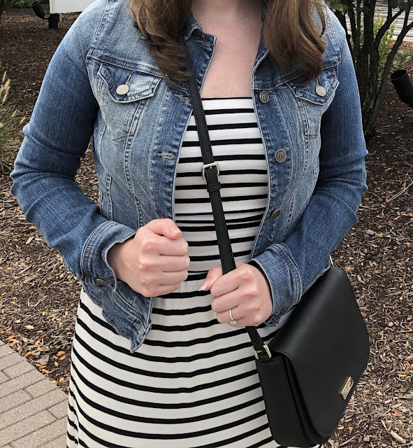 Model is wearing a black and white striped maxi dress with a denim jacket and simple black accessories.