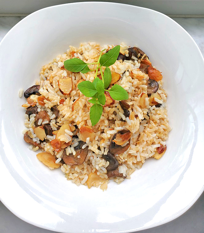 this is rice, almonds, mushrooms in a marsala sauce in a white plate with basil sprigs on top