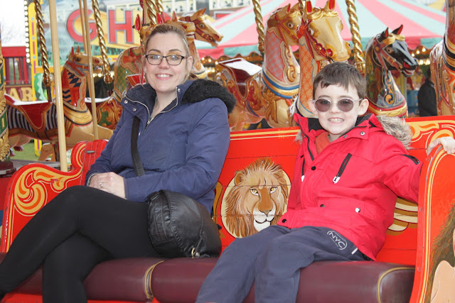 My sister and her son - my nephew, on the Gallopers ride, sitting in a carriage.