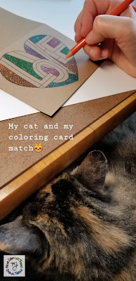 A calico cat is tucked on an artist's lap while she is coloring at a table.