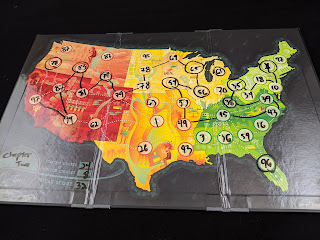 A closer view of one of the game boards, showing a variety of numbers written on the spaces for each state in dry-erase marker, with a route marked between several of these states. In the lower left corner, the band's name 'Chapter Two' has been written, next to the points (24 states + 8 circles = 32 points total).