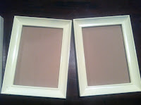 A close up of two picture frames painted white with brown, cloth napkins to be used as backing for the picture frames